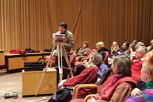 Bild zeigt Publikum und einen Teilnehmer während seines Redebeitrags