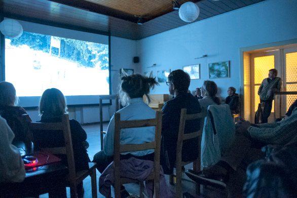 Bild zeigt Publikum, auf der Leinwand eine Filmszene