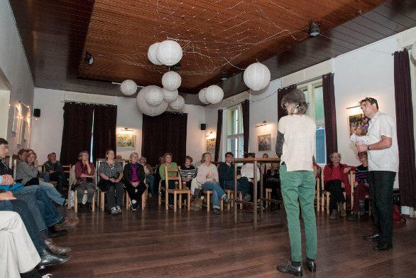 Bild zeigt Publikum, Moderator, Projektleiterin des Festivals STADTGESICHTER