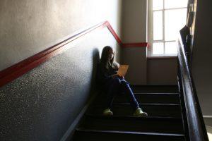 Mädchen liest im Treppenhaus
