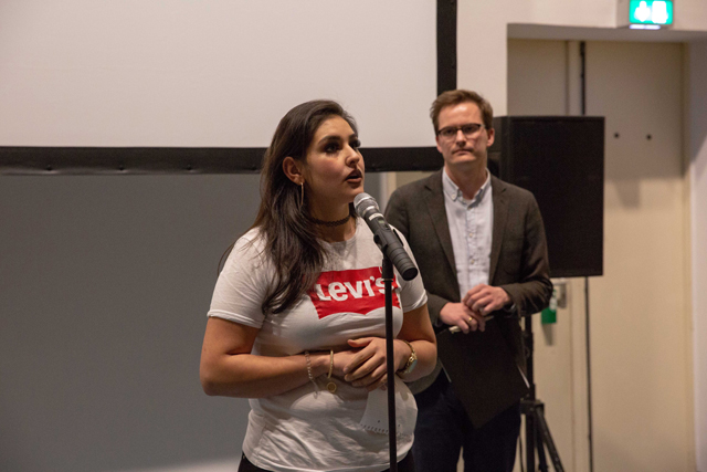 Bild zeigt eine Schülerin der Theodor-Heuss-Gemeinschaftsschule am Mikrofon, im Hintergrund Moderator Lukas Welz, AMCHA Deutschland