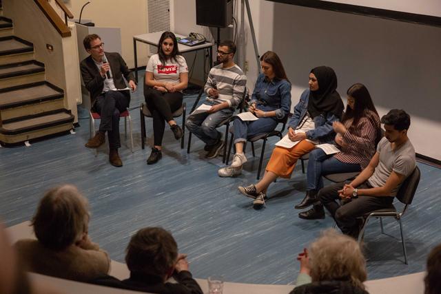 Bild zeigt Moderator Lukas Welz, AMCHA Deutschland im Gespräch mit Schüler*innen der Theodor-Heuss-Gemeinschaftsschule