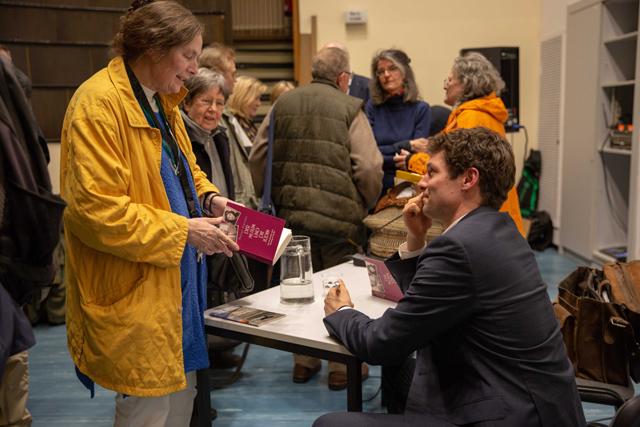 Bild zeigt Ronen Steinke im Gespräch mit einer Zuhörerin und signiert sein Buch