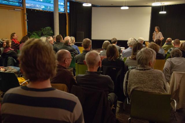 Bild zeigt das Publikum vor der Filmleinwand und Maren Dorner, die in das Thema einführt, vor der Vorführung