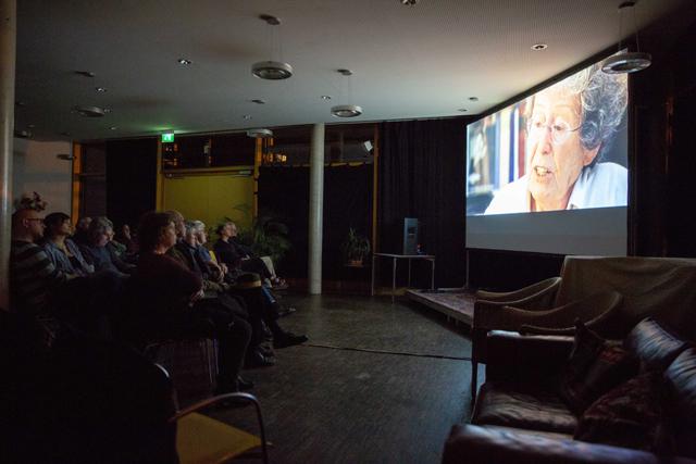 Bild zeigt das Auditorium und einen Filmausschnitt aus Die Unsichtbaren – Wir wollen leben